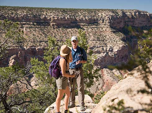 Pink® Jeep® tour guide and client standing along the edge of the Grand Canyon's Hermit Trail