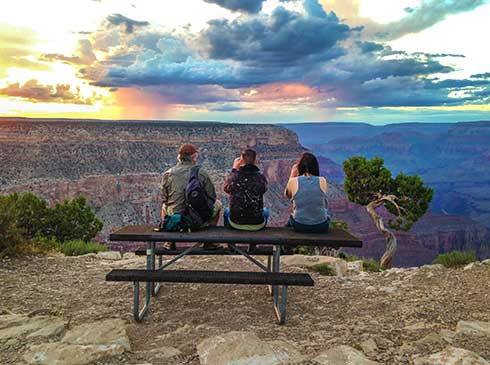 Three tourists seated atop picnic table watching sweeping rainbow colored sunset over Grand Canyon South Rim