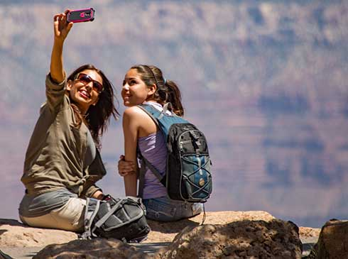 Mother and daughter seated along the Canyon's cliff edge taking a selfie during Hermits Rest Sunset Tour