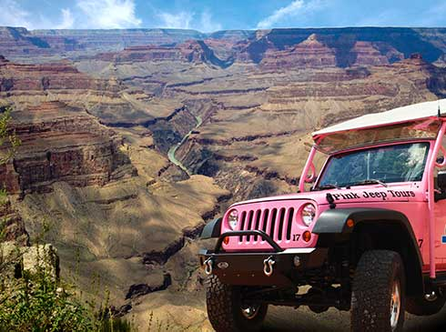 Pink® Jeep® parked in front of panoramic view of the Grand Canyon with Colorado River below