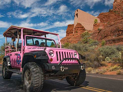 Pink® Jeep® wrangler with tour guide and guests passing the Chapel of the Holy Cross on Scenic Sedona Tour