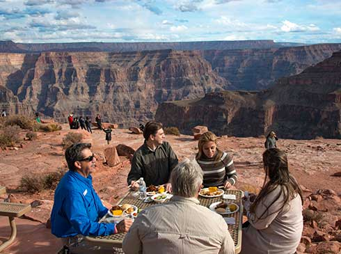 Grand Canyon West tour guide and guests enjoying barbeque lunch with canyon view