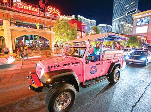 Guests tour the glittering Las Vegas Strip at night in an open-air Pink® Jeep®