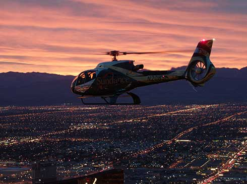 Luxury helicopter soars over the glittering city of Las Vegas, NV at night