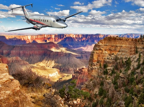 Maverick Airlines Beechcraft 1900D airplane soaring over the Grand Canyon