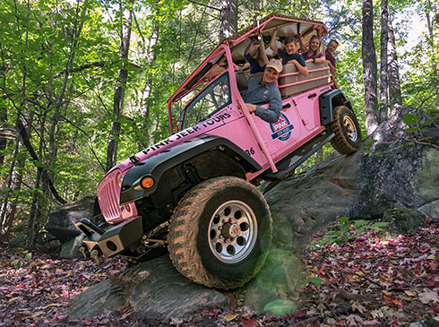 Vehicle with guests perched atop steep rocks during Pink Jeep's Roaring Fork Smoky Mountains tour