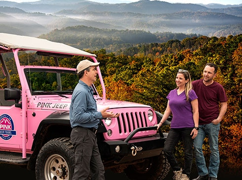 Pink® Jeep® certified guide talking with couple beside jeep with sweeping views of Smoky Mountains in background