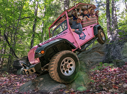 Tour guide and laughing guests in Jeep® wrangler, perched atop steep rock during 4x4 off-road adventure in Smoky Mountains