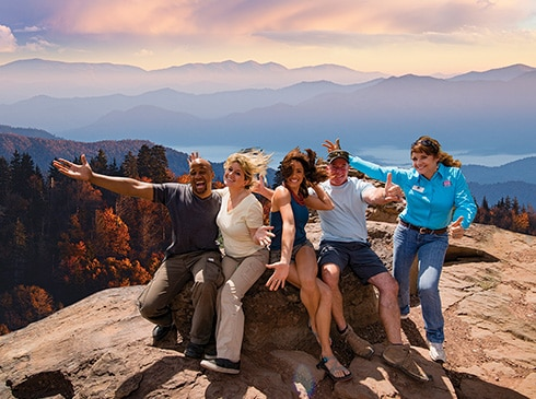Group photo of Pink Jeep tour guests and guide sitting atop rock, with Smoky Mountains sunset view in background