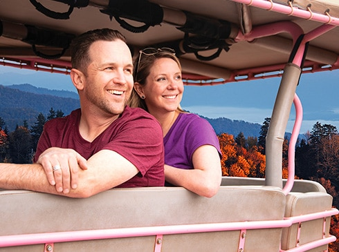 Smiling couple looking at views of Great Smoky Mountains from Pink® Jeep® wrangler