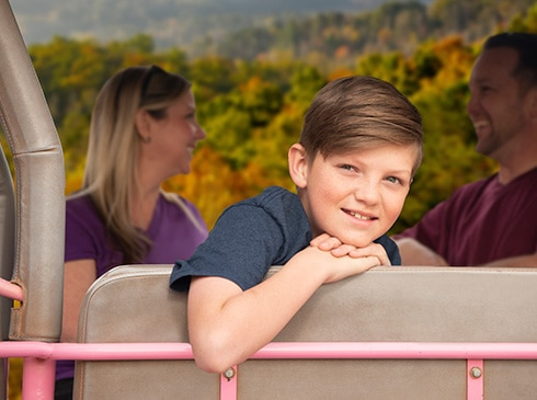 Young boy looking at camera from a Pink Jeep with parents and Smoky Mountains in background