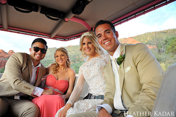 Close-up of bride, groom, best man and maid of honor sitting in backseat of Pink Jeep with Sedona in background