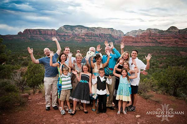 Newlyweds and family laughing and posing at Dry Creek Vista First Overlook with Secret Mountain Wilderness in distance