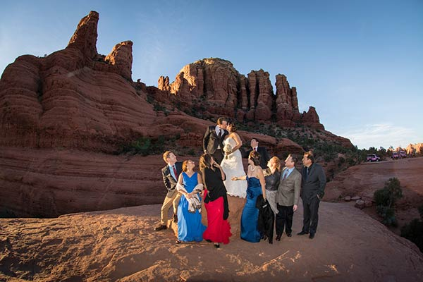 Wedding party with bride and groom kissing in late afternoon sunlight at Chicken Point, Sedona, AZ