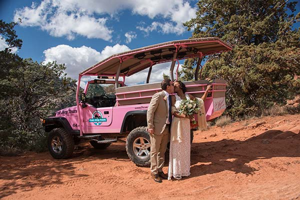 Newlyweds kissing by Pink Jeep on Scenic Sedona wedding tour
