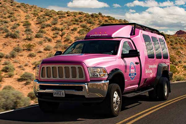Close-up of Pink Adventure Tour Trekker vehicle on highway during Las Vegas-Grand Canyon West tour.
