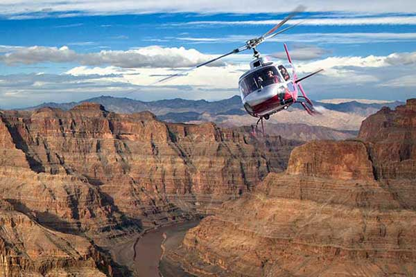 Helicopter soaring over Grand Canyon with beautiful blue sky