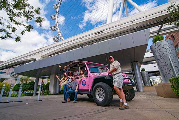 Las Vegas tour group standing by Pink Jeep parked by High Roller wheel