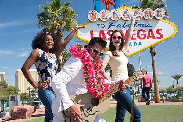 Two girls posing with Elvis by Welcome Las Vegas sign