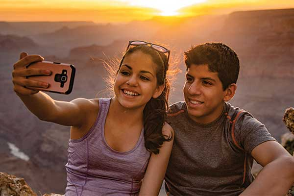 Teenagers taking selfie at Grand Canyon with sunset behind them