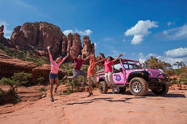 Family jumping on Sedona red rocks with Pink Jeep in background