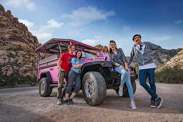 Family posing by Pink Jeep on Red Rock Canyon Rocky Gap tour