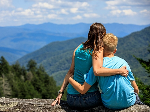 Mother and son embraced, seated on Newfound Gap Overlook wall looking towards the Smoky Mountains