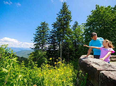 Father and daughter standing at Newfound Gap Overlook, looking out at Smoky Mountains scenery