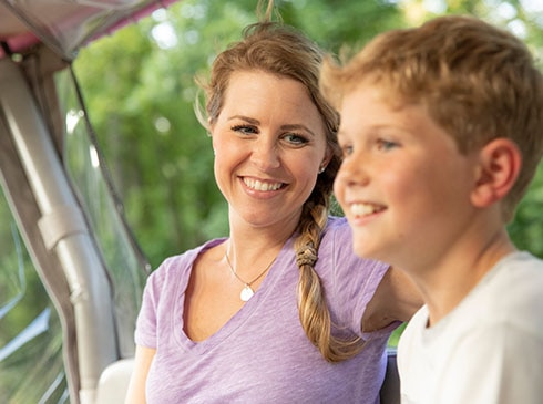 Close-up of smiling mother and son riding in back of Pink Jeep on the Roaring Fork Smoky Mountains tour