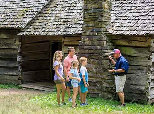Pink Jeep tour guide and family talking outside Ephraim Bales Cabin on Roaring Fork Smoky Mountains tour