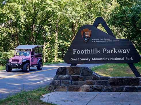 Close-up of Pink® Jeep® vehicle passing the Foothills Parkway sign in Smoky Mountains, Great Smoky Mountains National Park, TN