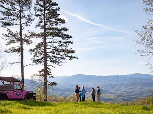 Foothills Parkway tour group standing in grassy filed viewing the Smoky Mountains, Pink Jeep and tall pines on left