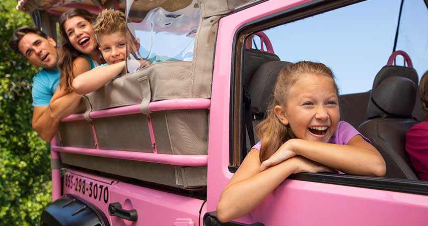 Family smiling and laughing hanging over side of Pink Jeep on private 4x4 off-road trail, Smoky Mountains, TNs,