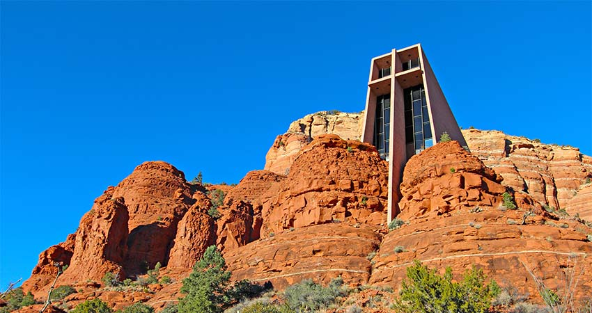 Chapel of the Holy Cross built into red rocks of Sedona with vibrant blue sky in background