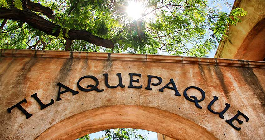Tlaquepaque Arts and Crafts Village archway sign with sun blazing through sycamore trees, Sedona, AZ