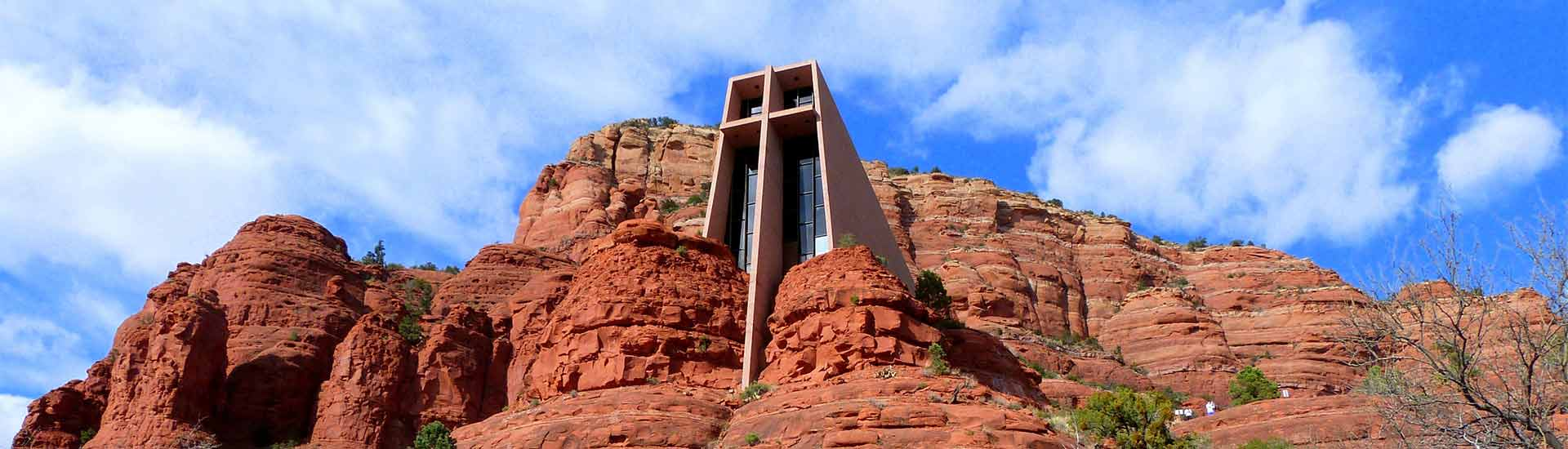 Chapel of the Holy Cross nestled into Sedona's red rocks with blue sky white clouds in back