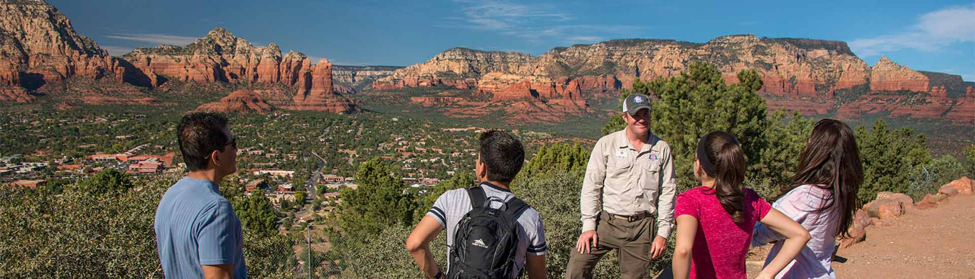 Pink Jeep guide and family on Sedona 360 Tour overlooking the town and red rocks from Airport Mesa Overlook