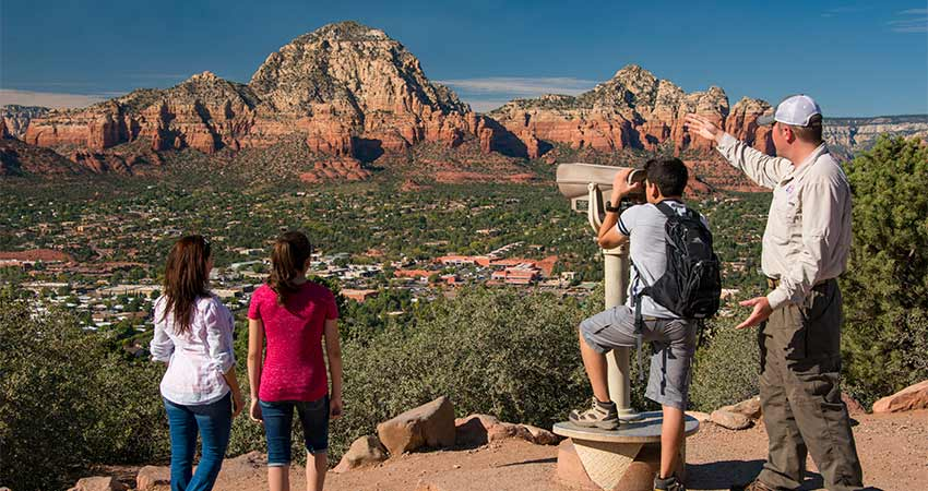 Pink Jeep guide pointing out Thunder Mountain with boy looking through telescope at Sedona's Airport Mesa Overlook