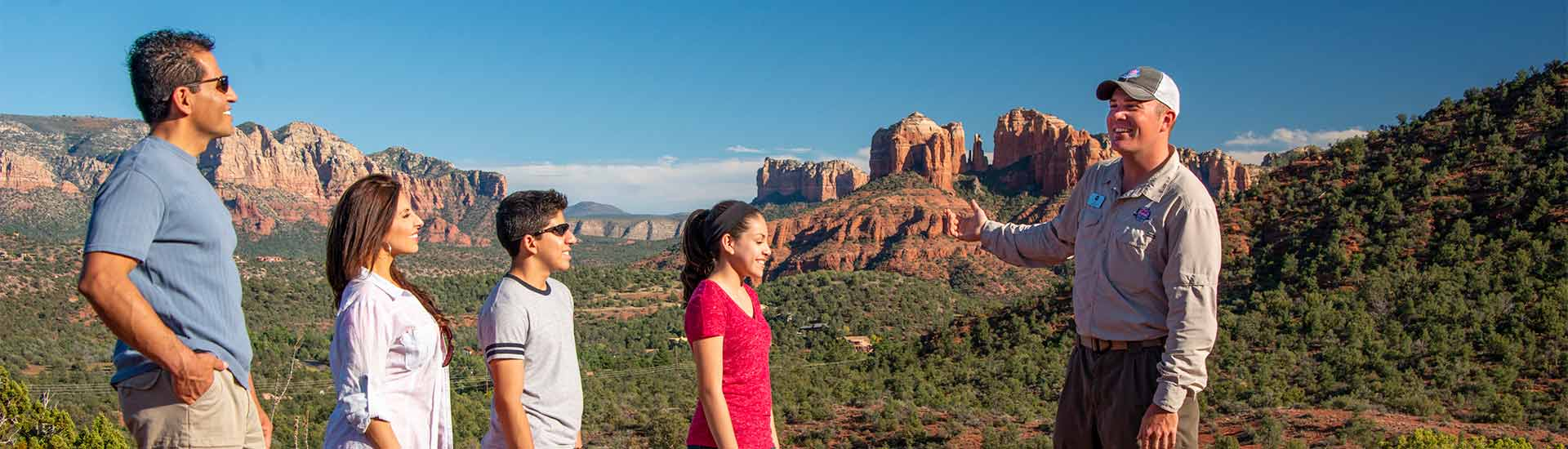 Pink® Adventure® Tour guide with family on Sedona 360 Tour at the Knolls overlooking Cathedral Rock