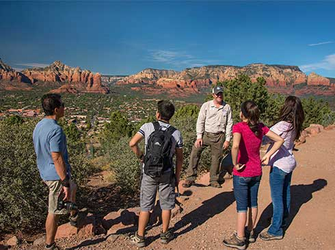 Pink Adventure Tour guide and Sedona 360 Tour guests at Airport Mesa Overlook with red rocks in distance