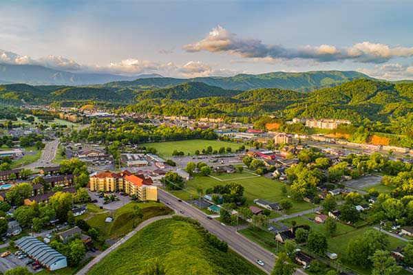 Aerial drone shot of Pigeon Forge and Sevierville, TN surround by vibrant green foothills of Smoky Mountains