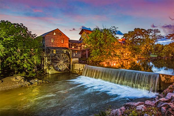 Sunrise view of the Old Mill, Pigeon Forge, TN with Little Pigeon River flowing in foreground
