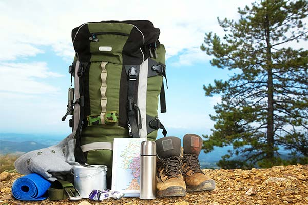 Hiking essentials with daypack and hiking shoes picture at top of mountain overlook
