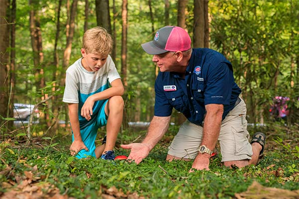 Pink Jeep guide kneeling on ground showing young boy wild mushrooms, Roaring Fork Smoky Mountains Tour