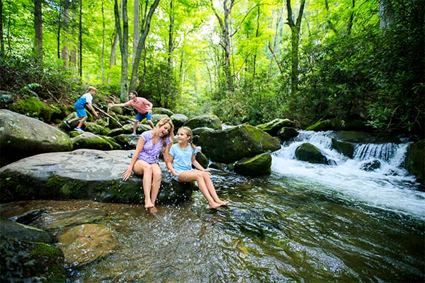 Family playing in mountain stream along the Roaring Fork Motor Nature Trail, GSMNP