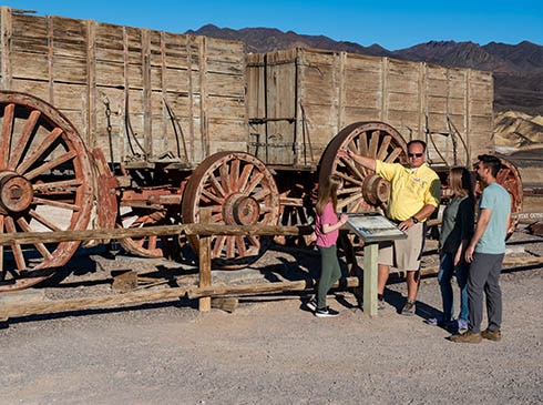 Pink Adventure Death Valley Tour guide and guests talking next to Twenty-Mule Team Wagon at Harmony Borax Works