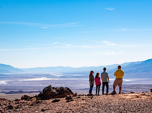 Pink Adventures' Death Valley Tour guests and guide looking out over the salt flats at Death Valley National Park