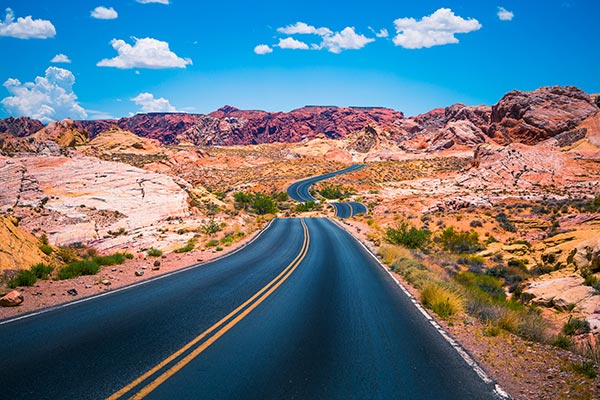 Vibrant view of White Domes Road winding towards red rock formations of Valley of Fire State Park, Nevada