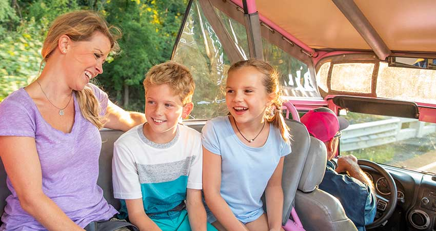 Mom and two kids smiling in back of Pink Jeep, driven by Smoky Mountains Valley and Views tour guide