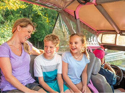 Mom and two kids smiling, seated in back of Pink Jeep driven by Smoky Mountains tour guide